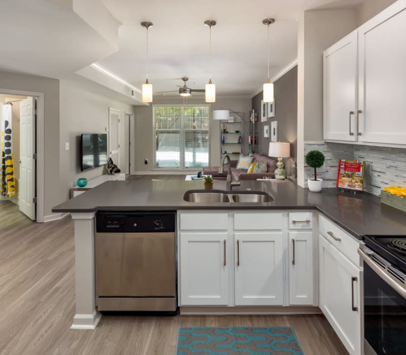 Bright kitchen with stainless steel appliances, modern countertops, and nickel brushed cabinet hardware at Marq on Ponce in Atlanta, Georgia