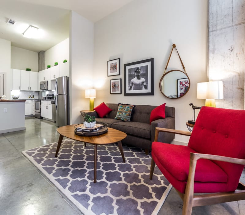 Open living room with modern furnishings and bright kitchen in background at Marq on Burnet in Austin, Texas