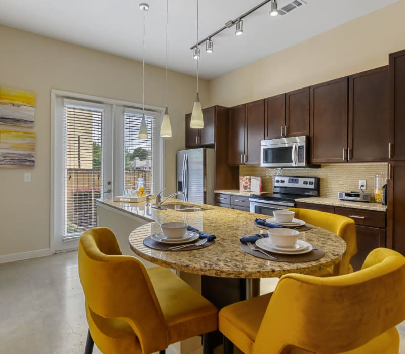 Granite dining table top off kitchen sink island with cushioned chairs surrounding at The 704 in Austin, Texas