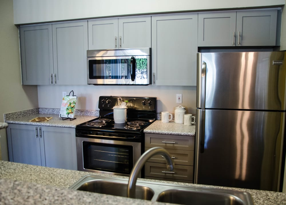 grey cabinets kitchen photo with stainless steel appliances at Wildreed Apartments in Everett, WA