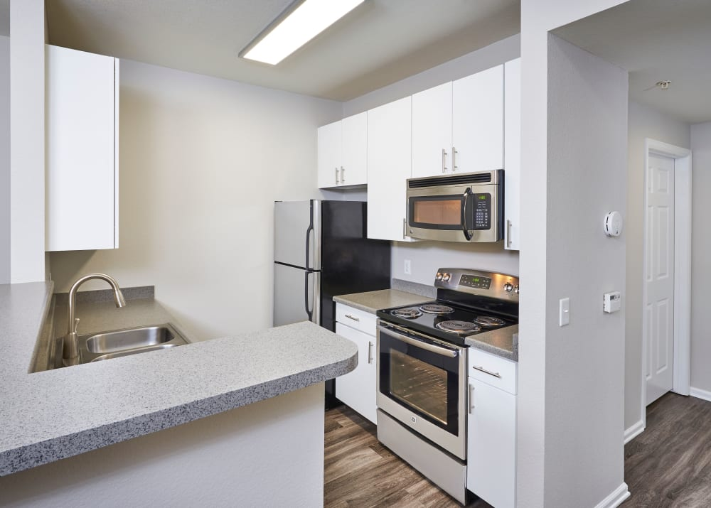 new white renovation cabinetry with stainless steel appliances at Bear Valley Park in Denver, Colorado