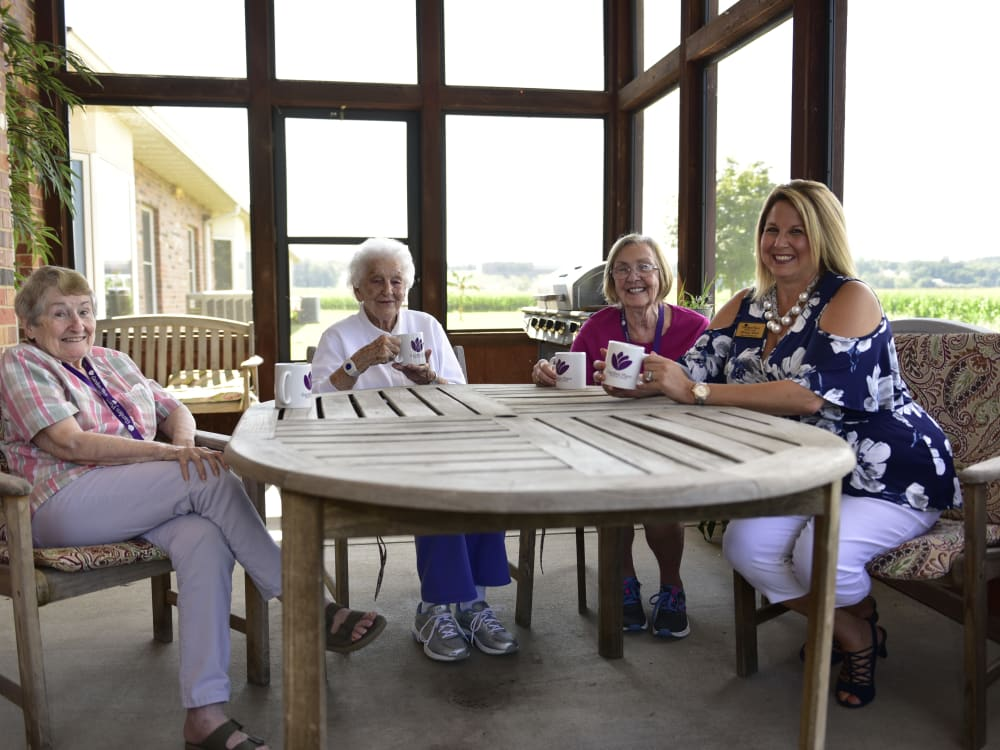 Residents and a staff member relaxing on a covered patio at Garden Place Columbia in Columbia, Illinois.