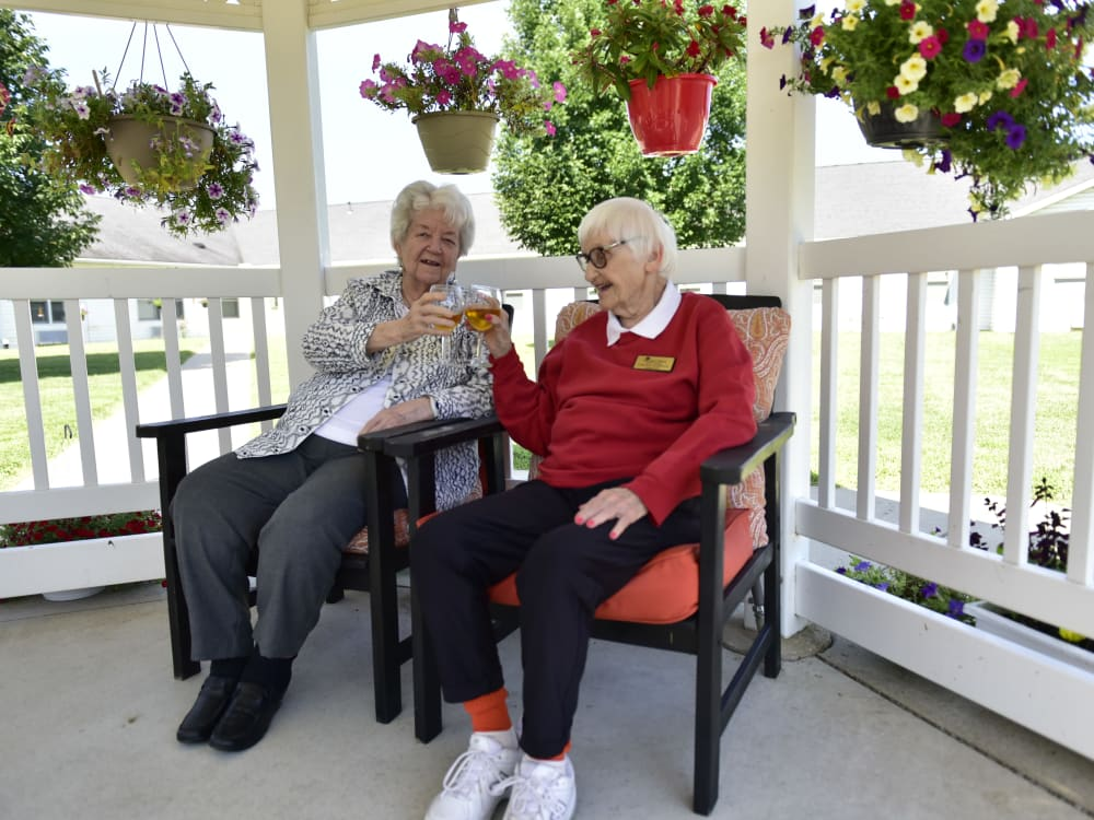 Two residents having a beverage on the patio at Garden Place Columbia in Columbia, Illinois.