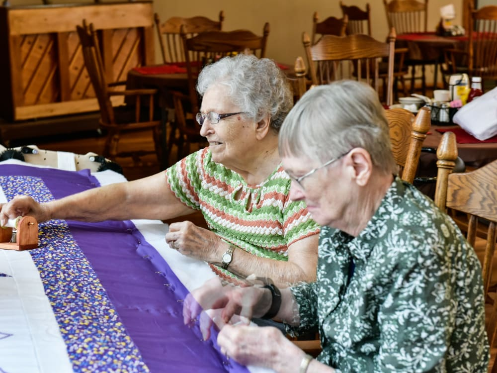 Two residents making a quilt at Garden Place Red Bud in Red Bud, Illinois.