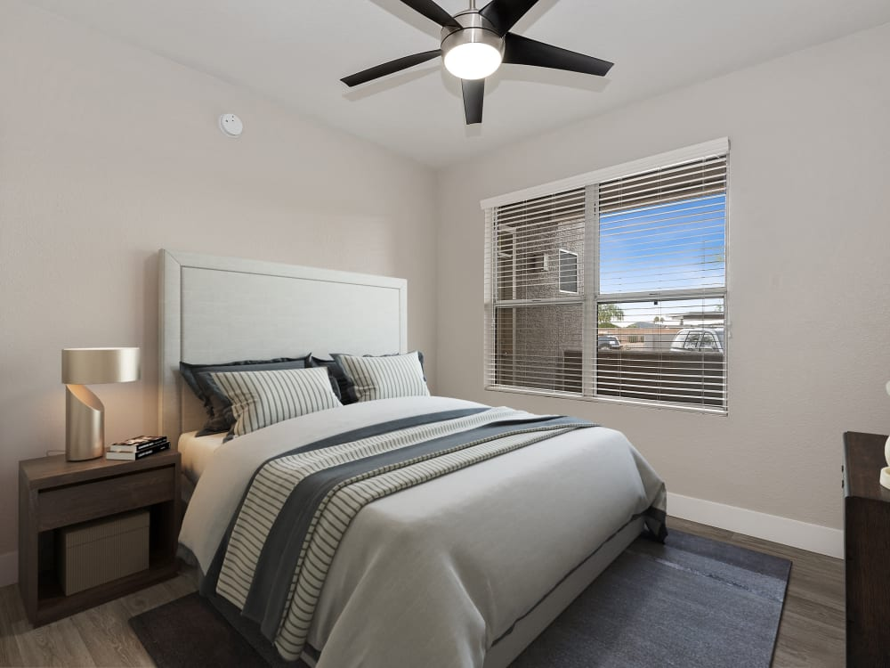 Bedroom with ceiling fan and large window for natural light at The Retreat Apartments in Phoenix, AZ