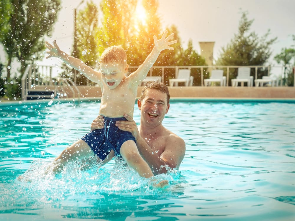 Father and his kid in the pool at TerraLane on Cotton in Surprise, Arizona
