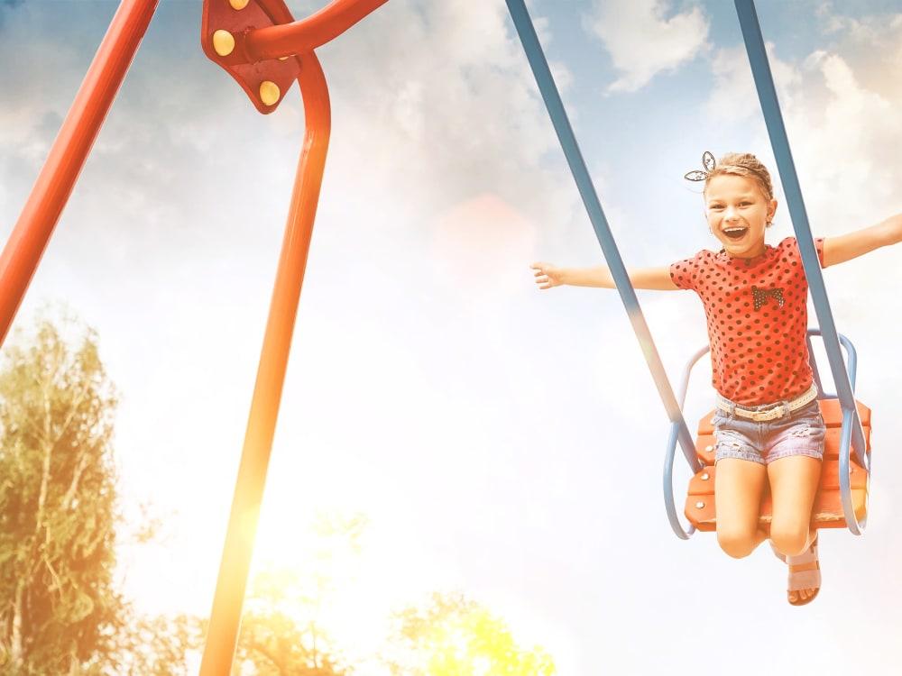 Kid on a swing at TerraLane on Cotton in Surprise, Arizona