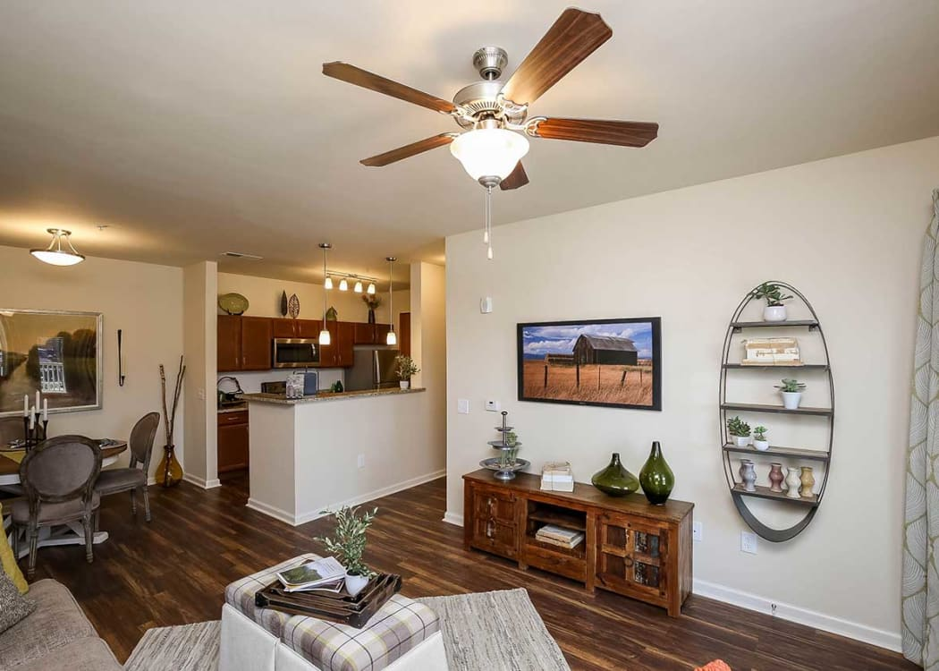 Cozy living room with wood-style flooring in a model home at Commonwealth at 31 in Spring Hill, Tennessee
