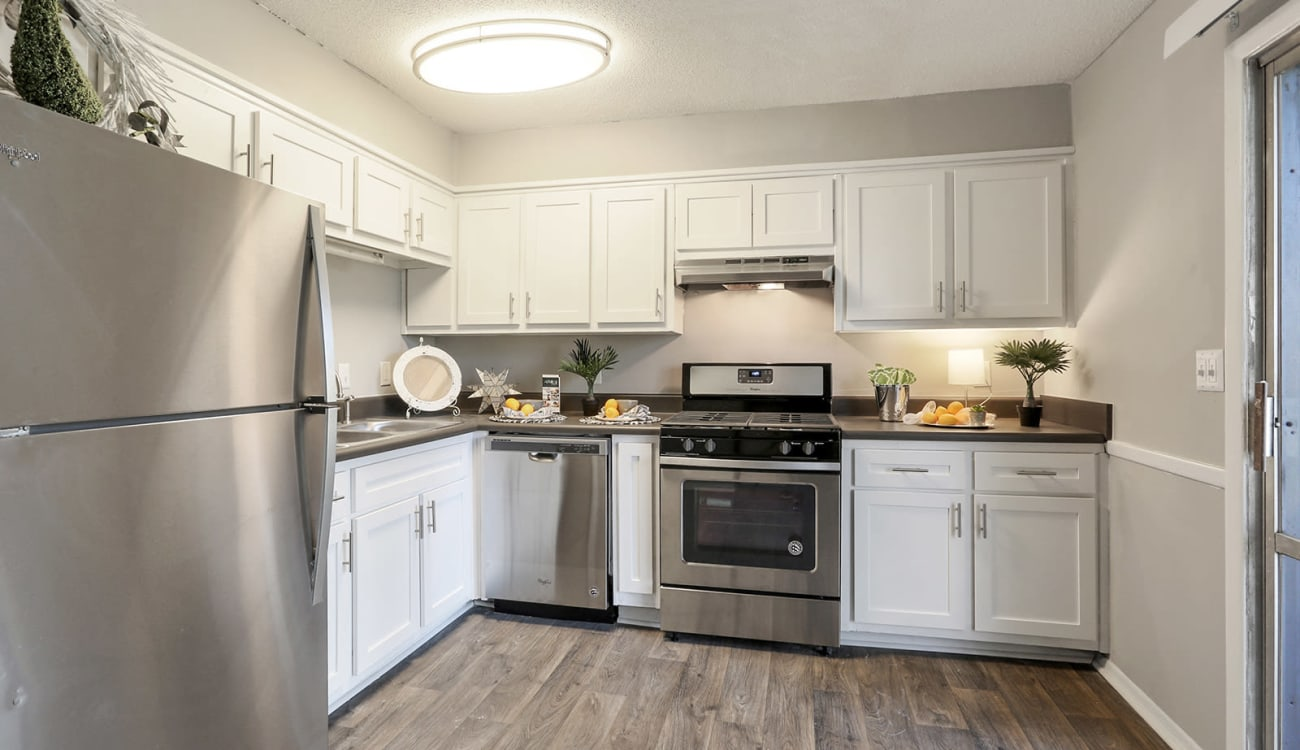 Model home's kitchen with stainless-steel appliances at Alturas Embry Hills in Doraville, Georgia