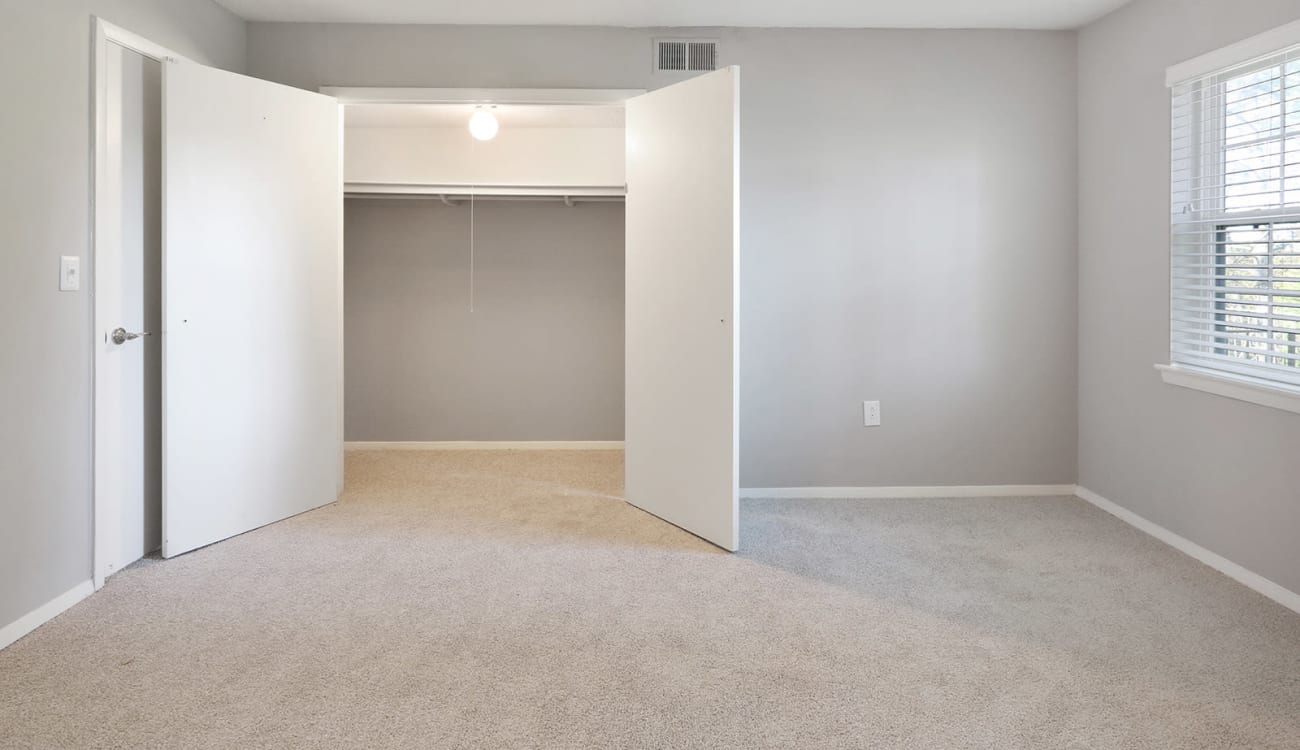 Large primary bedroom with ample closet space in an apartment at Alturas Embry Hills in Doraville, Georgia
