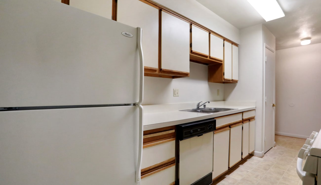 Kitchen with white appliances at Peppertree Apartments in Winchester, Virginia