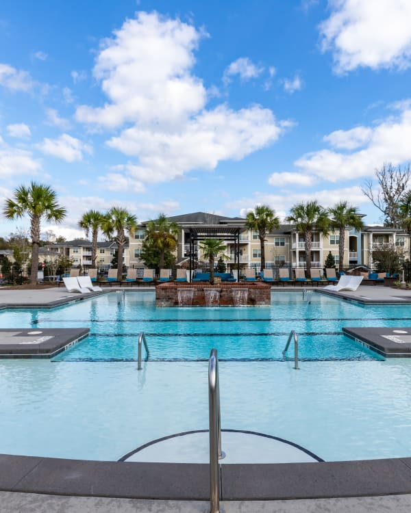 Swimming pool with an island of vegetation at Ansley Commons Apartment Homes in Ladson, South Carolina