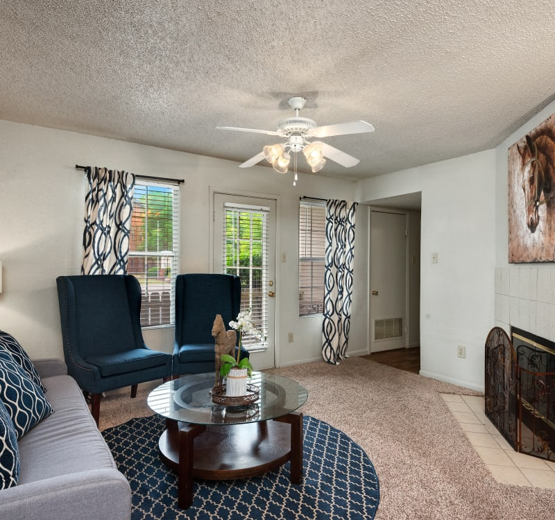 Wood-burning fireplace and a ceiling fan in a model home's living space at The Mansion in Independence, Missouri