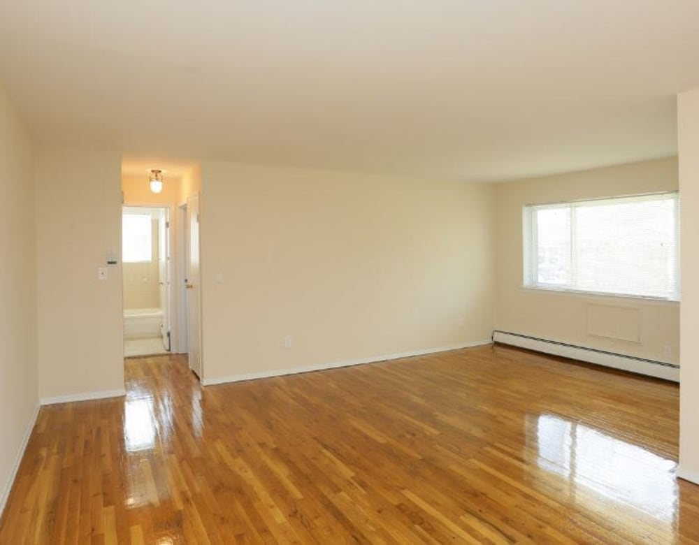 Bedroom with hardwood flooring and lots of natural light at Brixton Lane in Levittown, New York