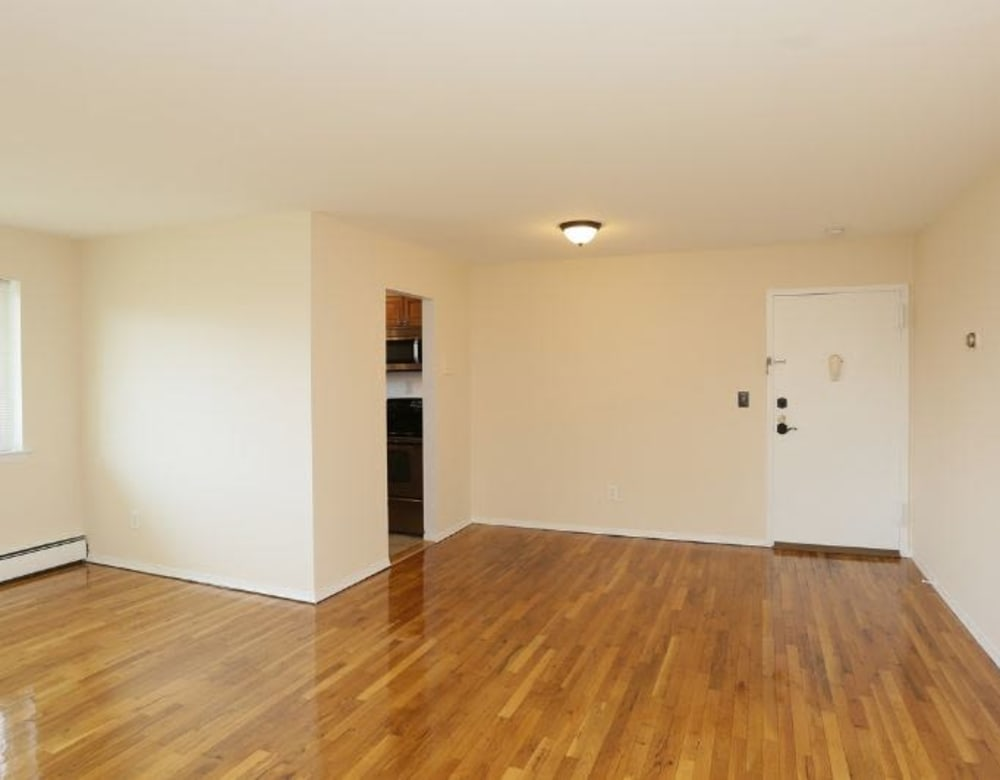 Living room with hardwood flooring at Brixton Lane in Levittown, New York