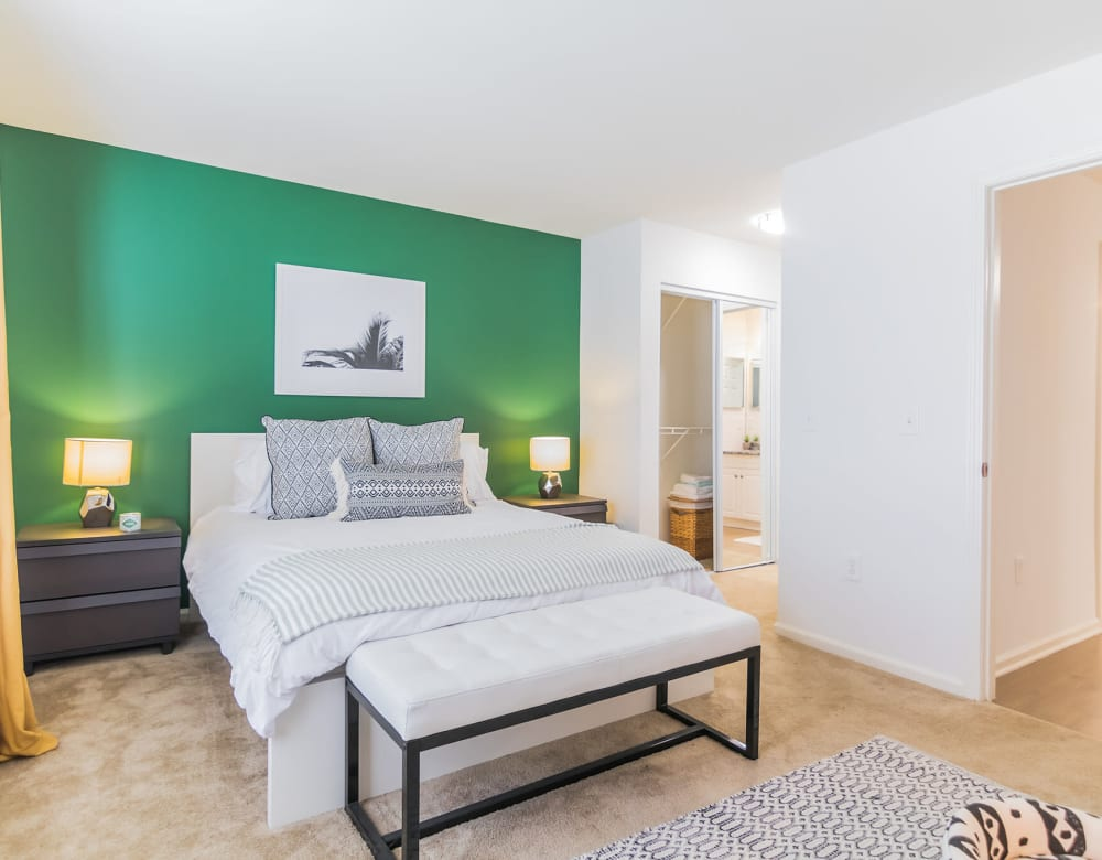 Comfortable bedroom with accent wall, hardwood floors and easy bathroom access In an apartment at Eagle Rock Apartments at Freehold in Freehold, New Jersey