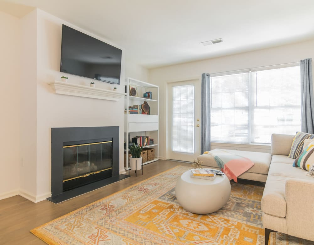 Living room featuring a fireplace and large screen TV over the mantle in an apartment at Eagle Rock Apartments at Freehold in Freehold, New Jersey