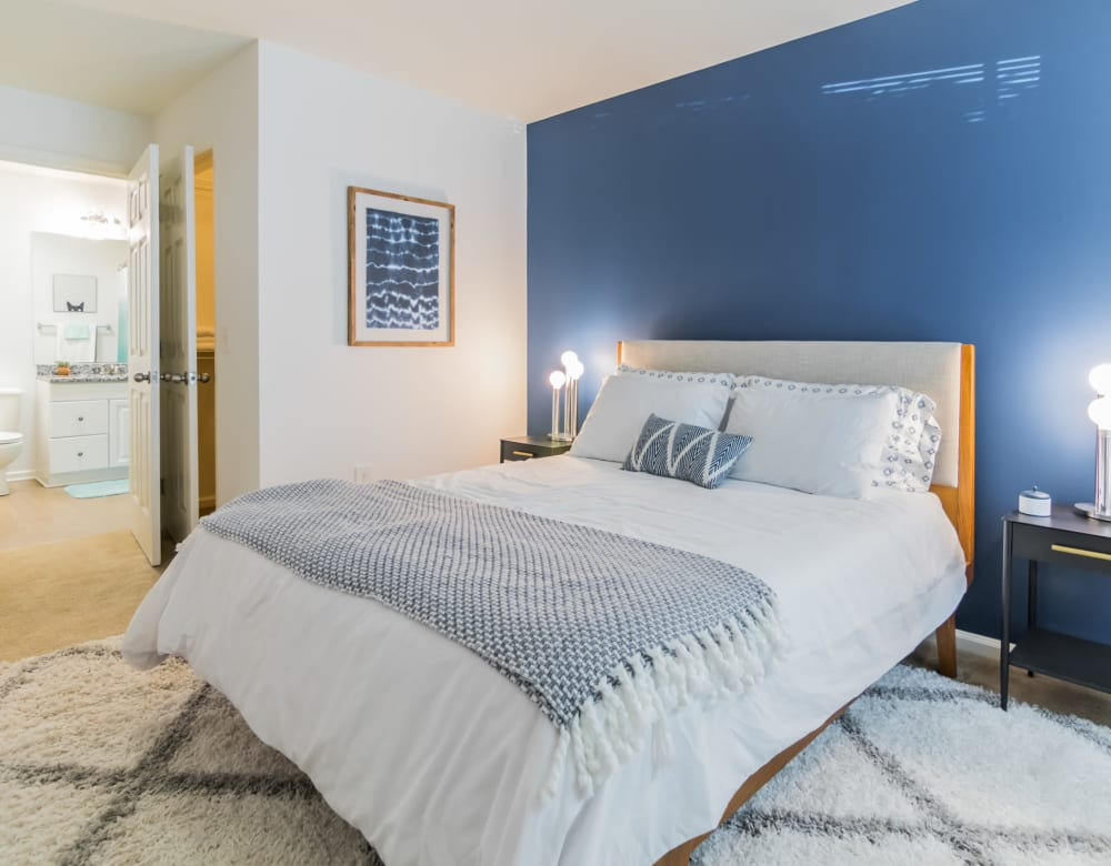 Stylish bedroom featuring an accent wall and large comfortable bed at Eagle Rock Apartments at Freehold in Freehold, New Jersey