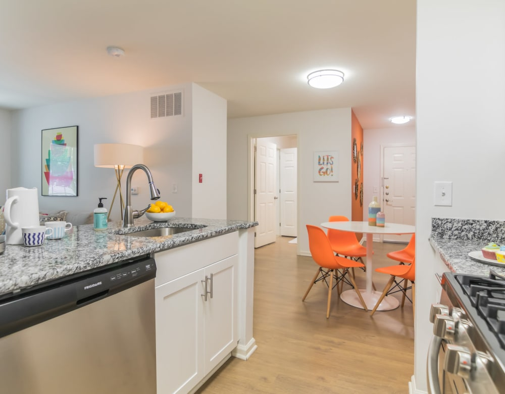 Kitchen with stainless steel appliances with bright colored chairs in dining room and art on the wall in the living room in an apartment at Eagle Rock Apartments at Freehold in Freehold, New Jersey