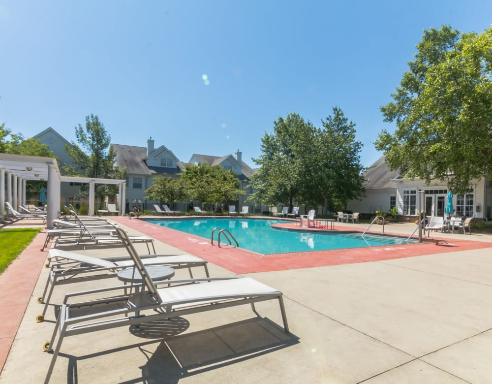 Community pool with mature trees and lounge chairs at Eagle Rock Apartments at Freehold in Freehold, New Jersey