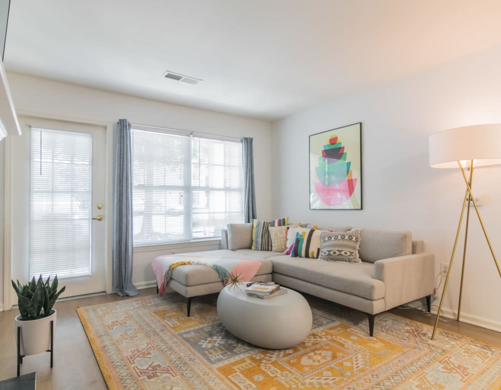 Couch seating with ample natural light from large windows in a living room  at Eagle Rock Apartments at Freehold in Freehold, New Jersey