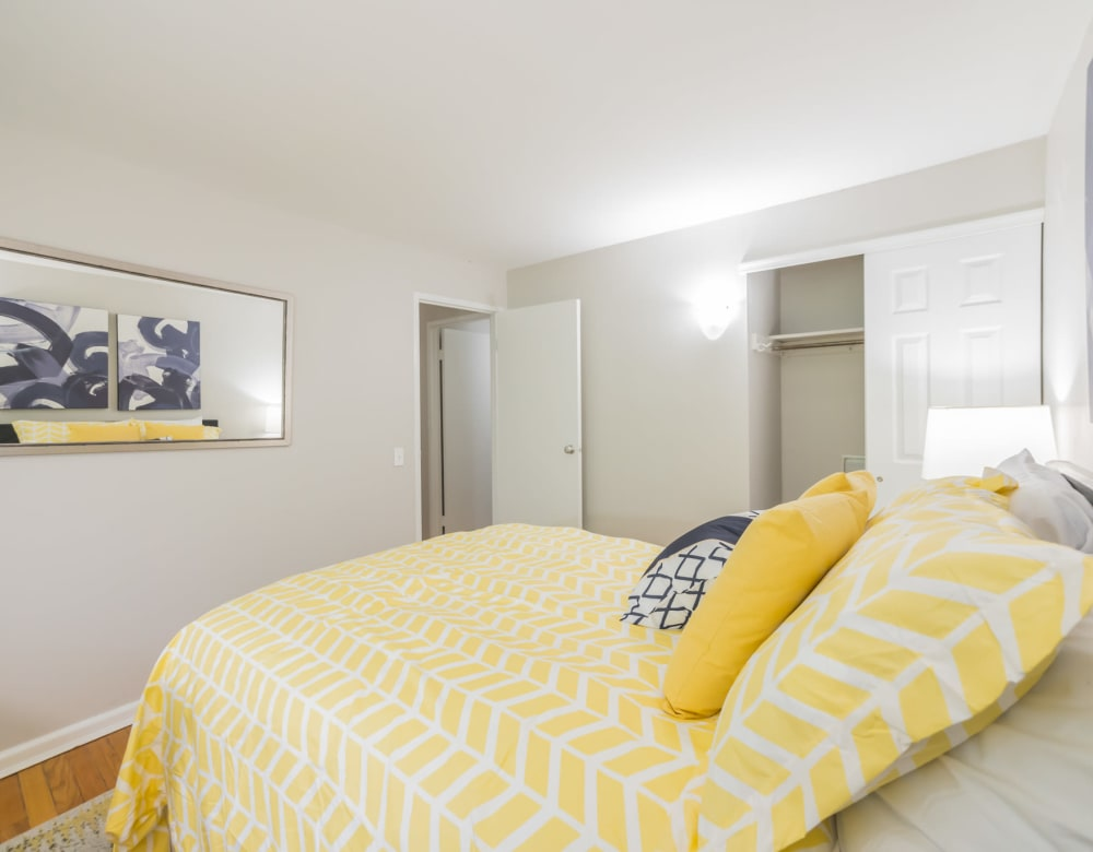 Bright yellow bedspread and art on the walls in this comfortable bedroom in an apartment  at Cherokee Apartments in Philadelphia, Pennsylvania