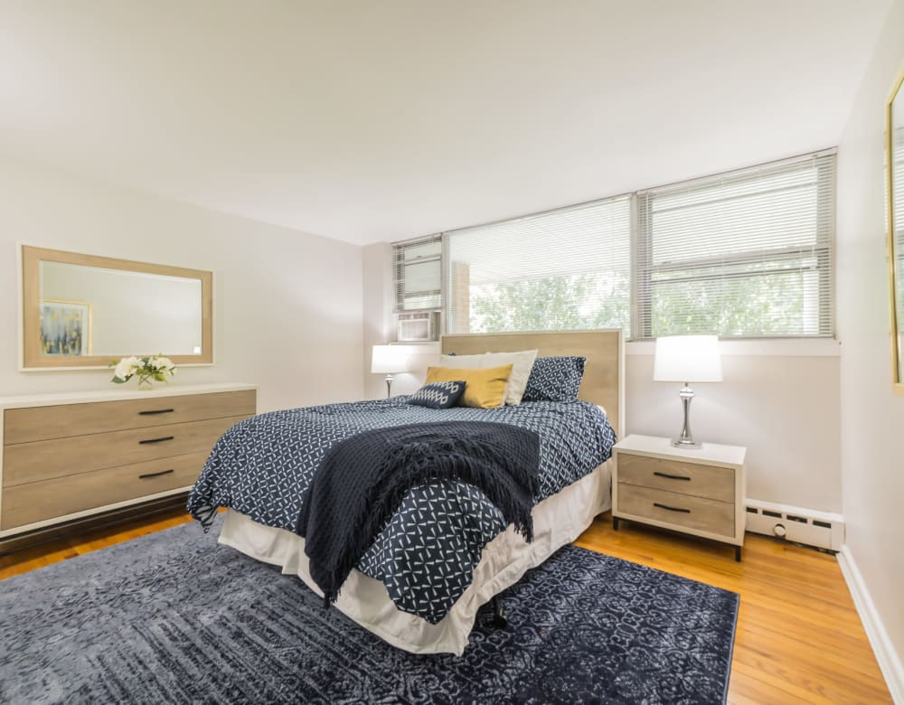 A spacious bedroom with ample natural light from large windows features Modern furnishings and hardwood floors in an apartment at Cherokee Apartments in Philadelphia, Pennsylvania