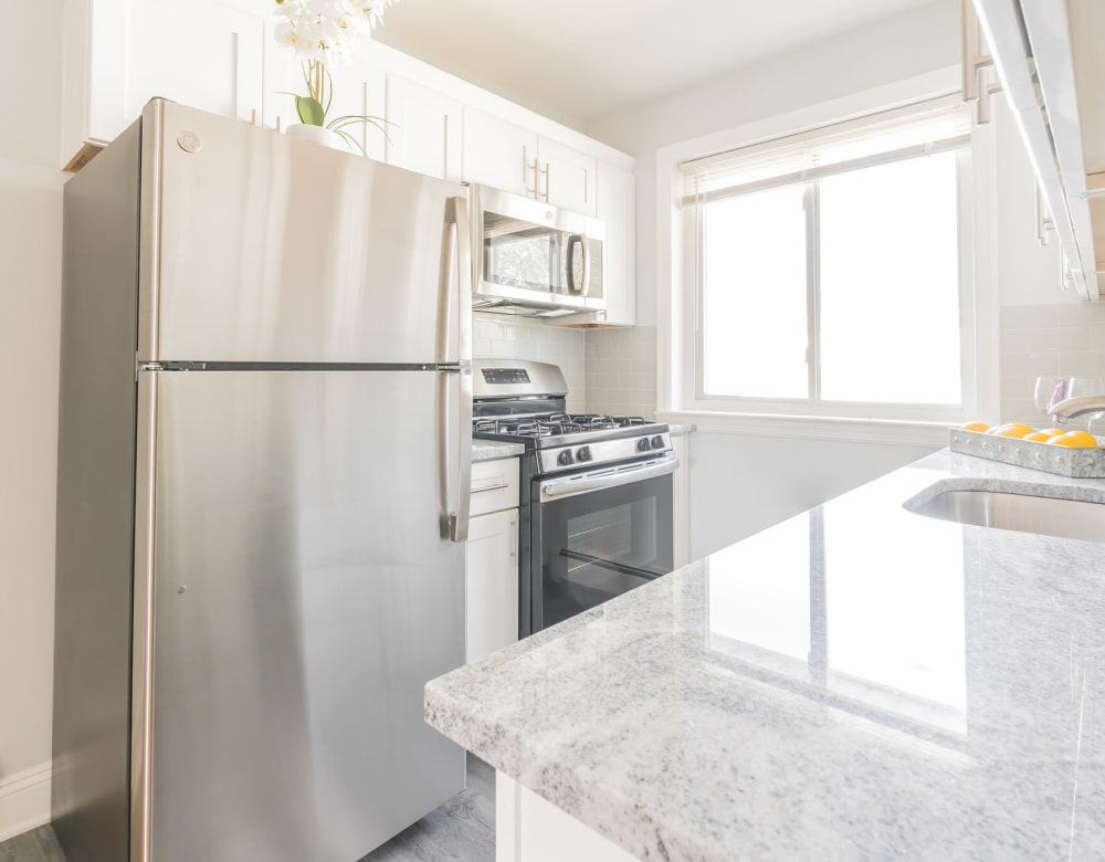 Kitchen of unit at Bellmore Manor Gardens with stainless appliances and granite counter tops