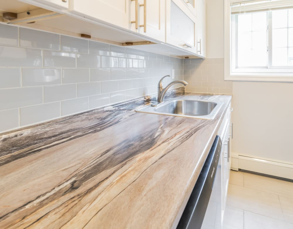 Bright kitchen with granite counter tops at Eagle Rock Apartments at Carle Place in Carle Place, New York