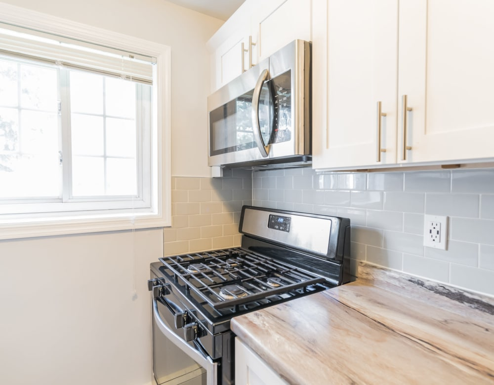 Sleek modern kitchen with stainless appliances at Eagle Rock Apartments at Carle Place in Carle Place, New York