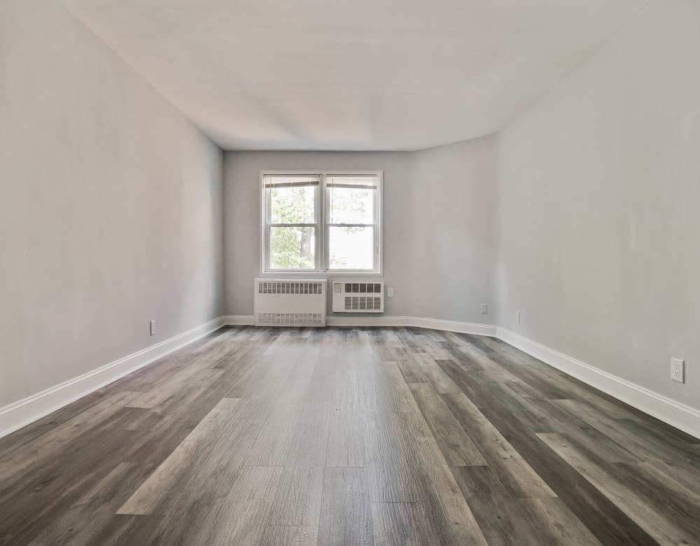 Open room with wood floors at Bergen Apartments in Freeport, New York