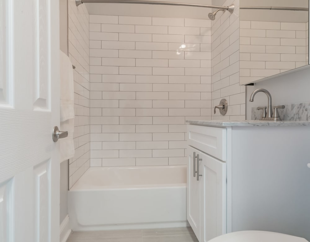 Bathroom featuring white subway tile at Bergen Apartments in Freeport, New York