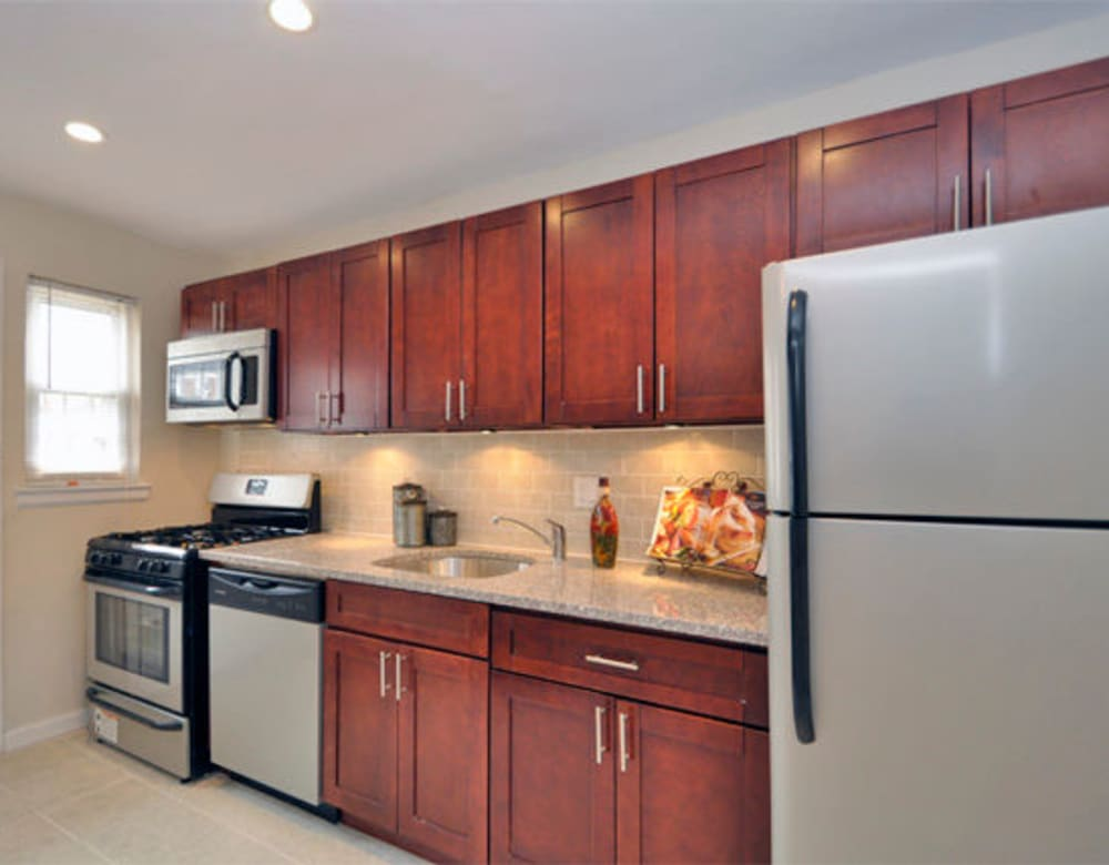Cherry red wood cabinets and stainless steel appliances in the kitchen at Eagle Rock Apartments at Maplewood in Maplewood, New Jersey