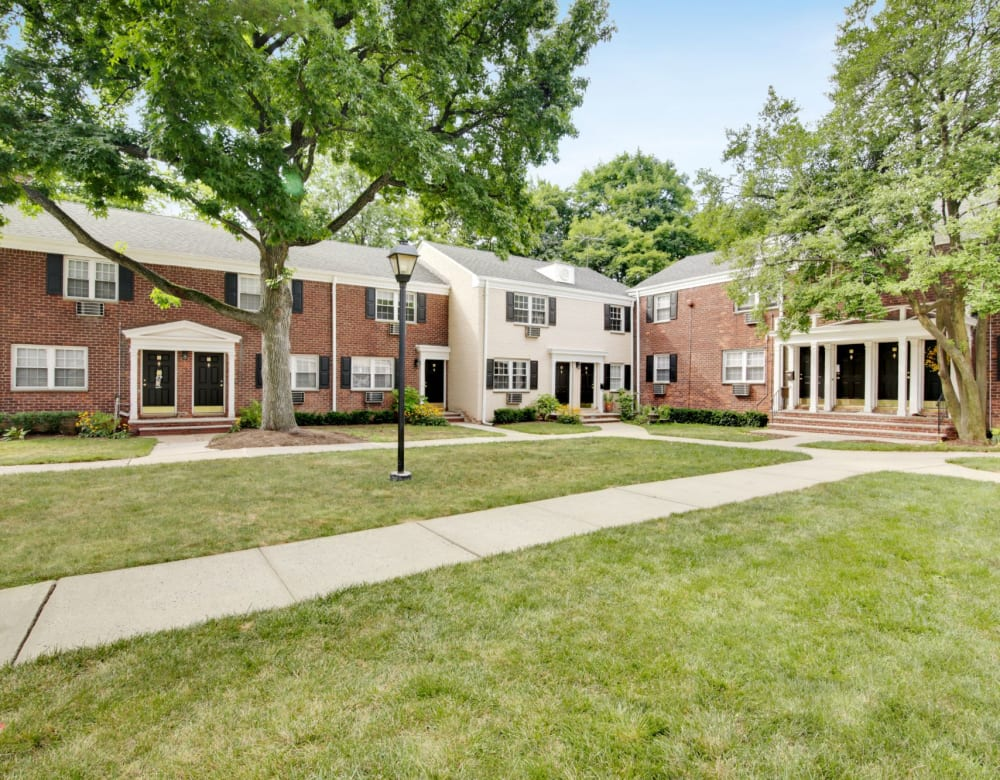 Exterior courtyard with a large grass area and lots of trees for shade at Eagle Rock Apartments at Maplewood in Maplewood, New Jersey