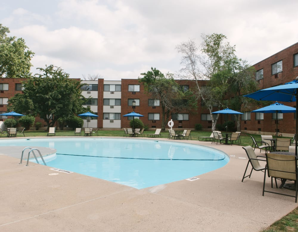 Large refreshing swimming pool with tables and chairs around it for guests to relax in at Eagle Rock Apartments at West Hartford in West Hartford, Connecticut