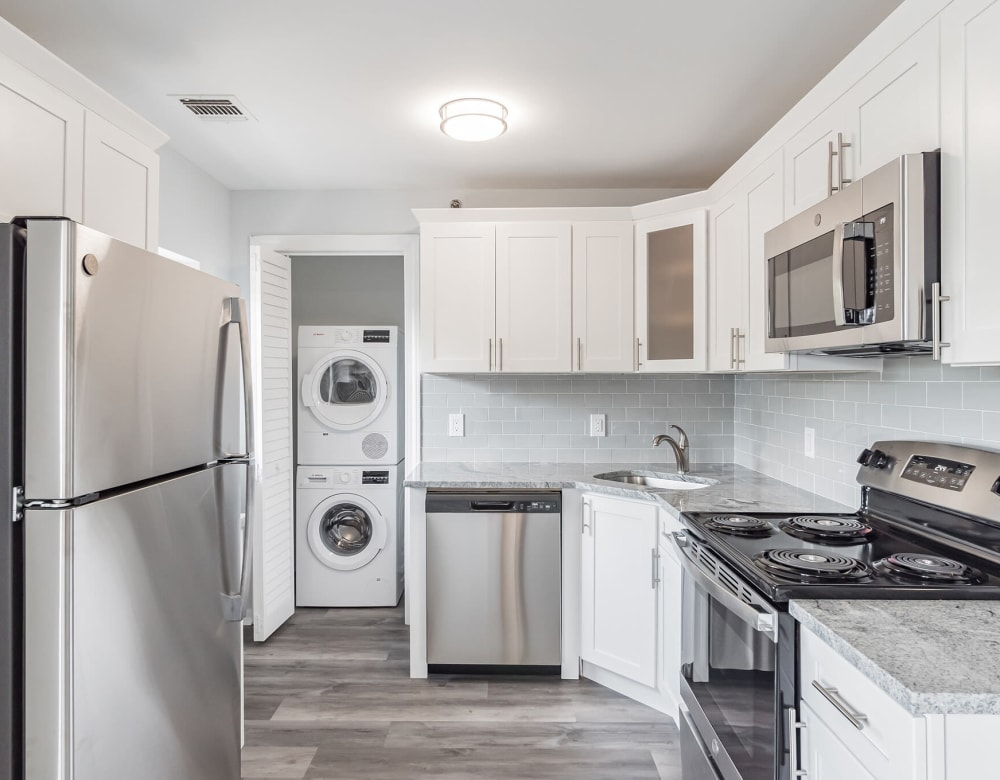 An apartment kitchen with washer and dryer at Bunt Commons III in Amityville, New York