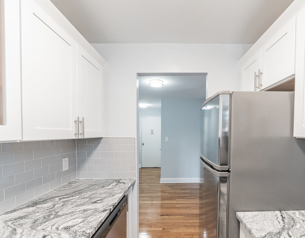 Kitchen connects to living room at Eagle Rock Apartments at Carle Place in Carle Place, New York