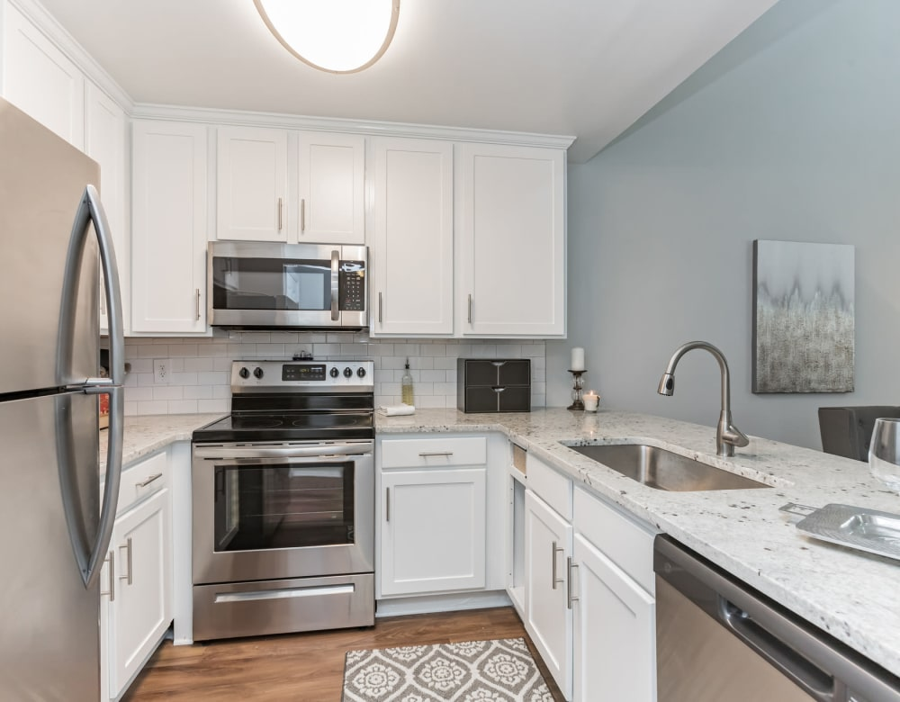 Model kitchen with granite island counter at Eagle Rock Apartments at Columbia in Columbia, Maryland