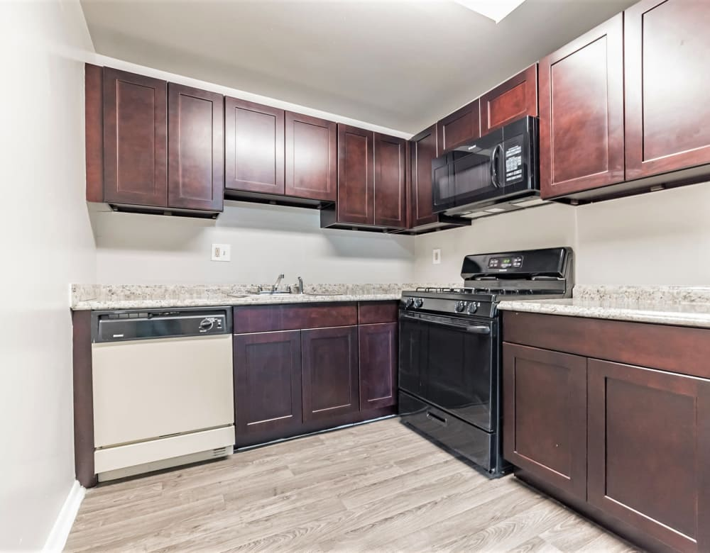 Cherry wood cabinetry and sleek black appliances in an apartment's kitchen at Eagle Rock Apartments at Towson in Towson, Maryland