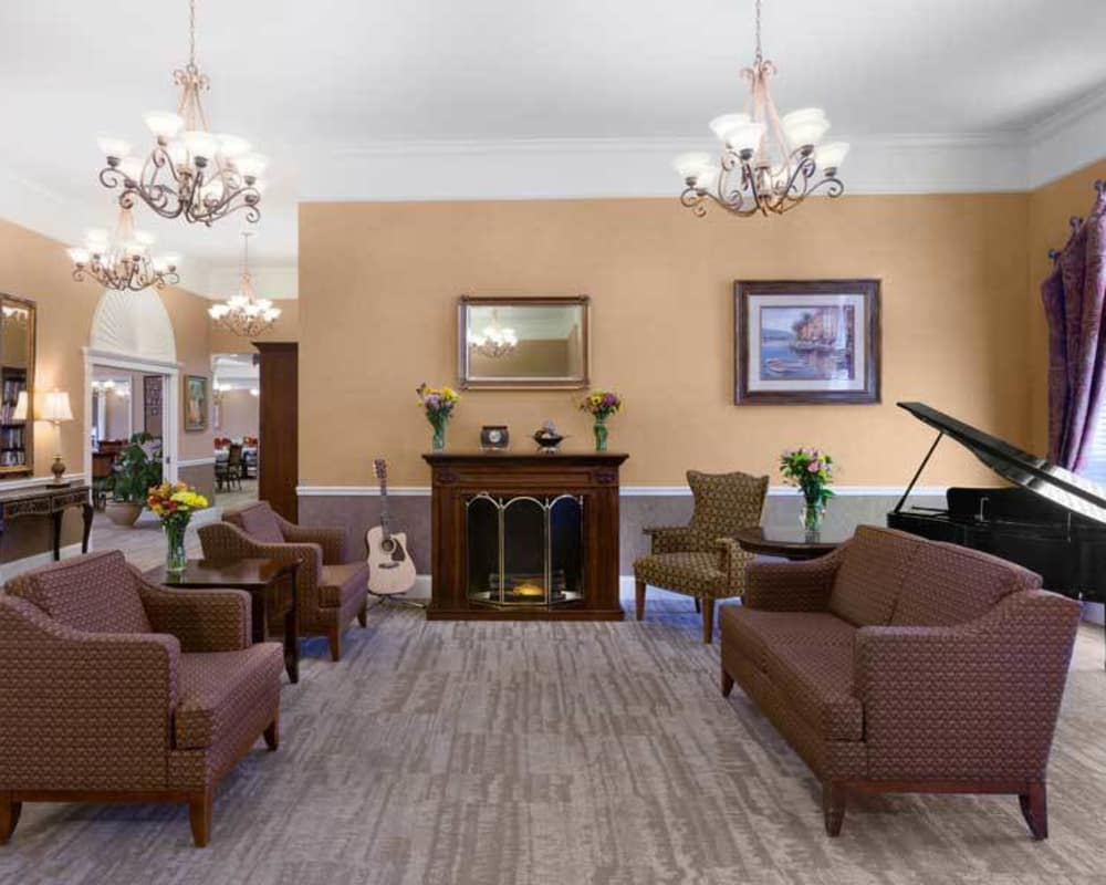 Cozy lounge area with a piano and fireside seating at Tiger Place in Columbia, Missouri