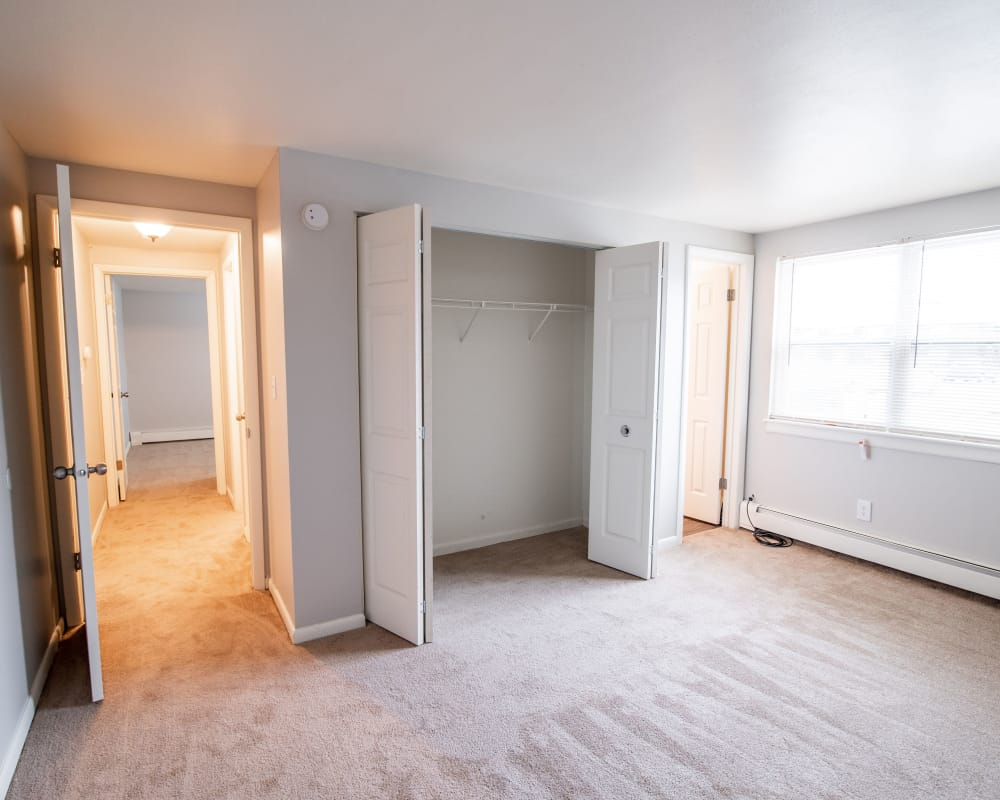 Naturally well-lit bedroom with closet at Village Green Apartments in Baldwinsville, NY