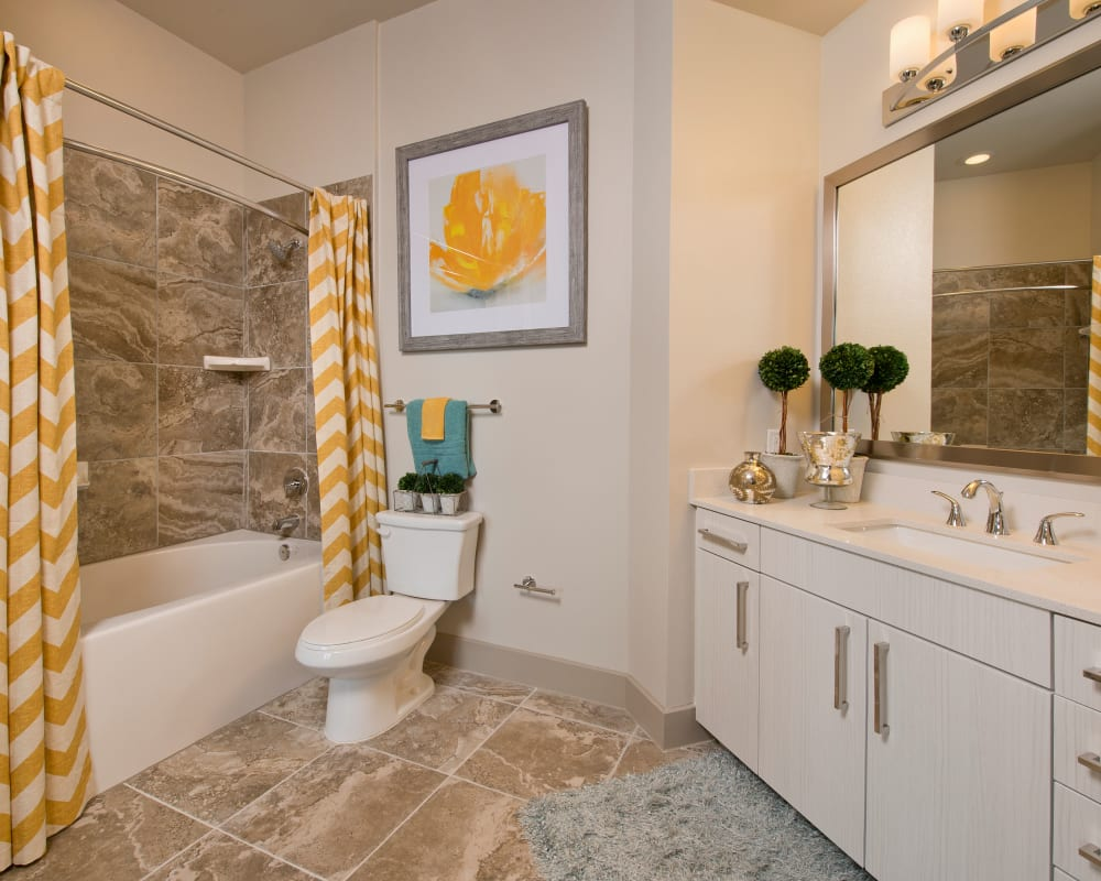 Model bathroom with yellow accents at Vargos on the Lake in Houston, Texas