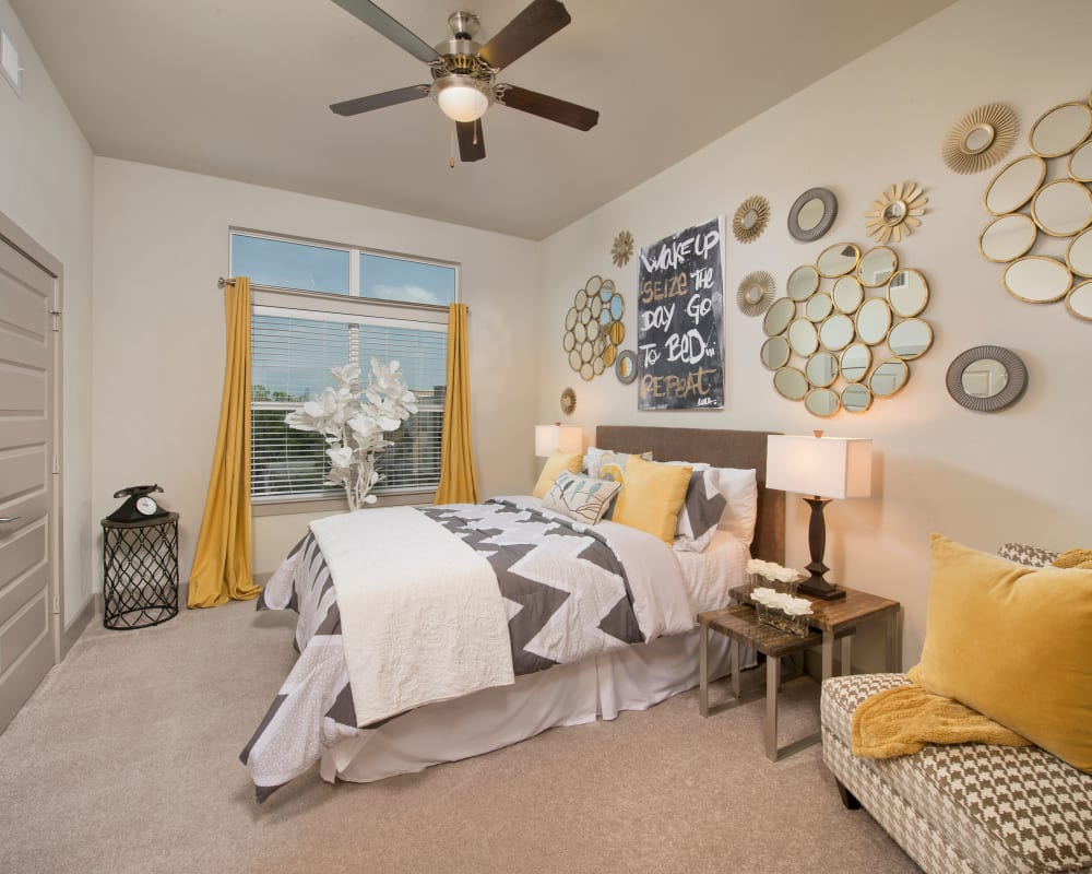 Model bedroom with yellow accents at Vargos on the Lake in Houston, Texas
