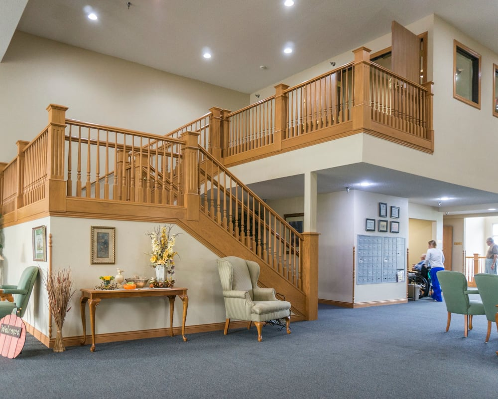 Spacious main entrance with elaborate staircase at Prairie Meadows Senior Living in Kasson, Minnesota.