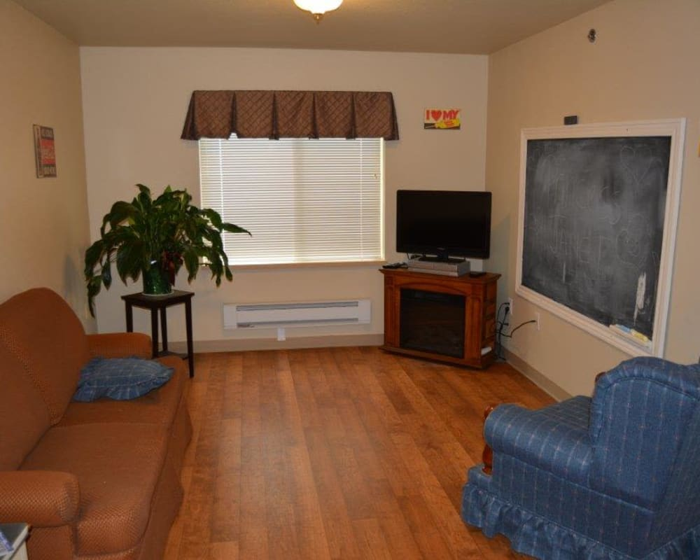 Resident living room with hardwood style floors at Courtyard Estates at Hawthorne Crossing in Bondurant, Iowa.
