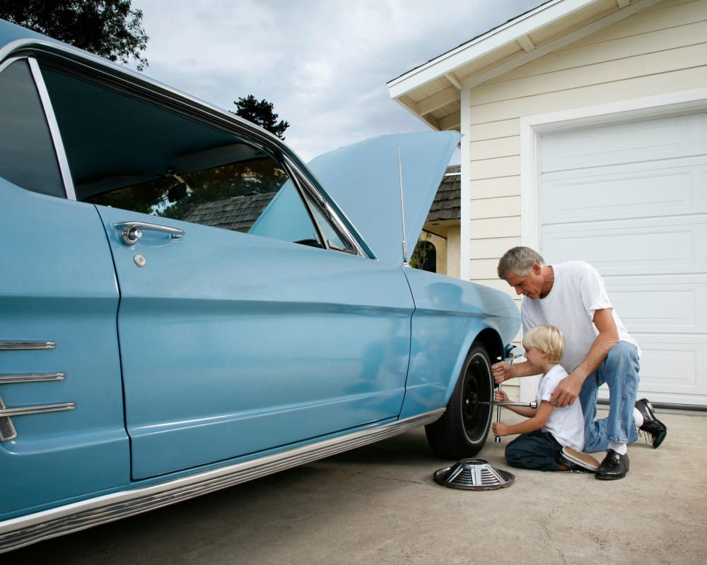 A father and son working on a classic car being stored at STOR-N-LOCK Self Storage in Palm Desert, California