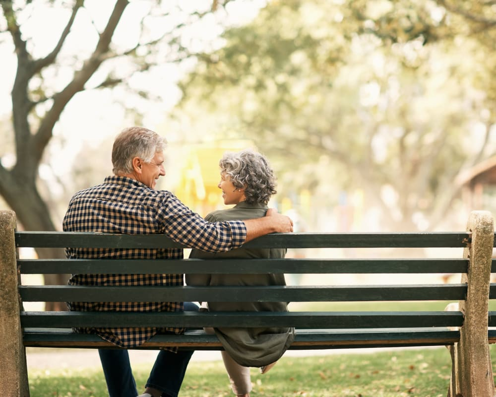 Resident couple sitting on a bench outside Edencrest at Green Meadows in Johnston, Iowa.