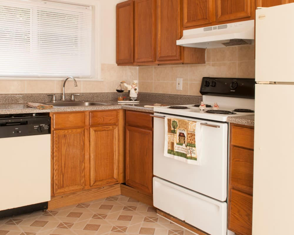Kitchen with wooden cabinets at Alpine Court East Apartments in Lindenwold, New Jersey