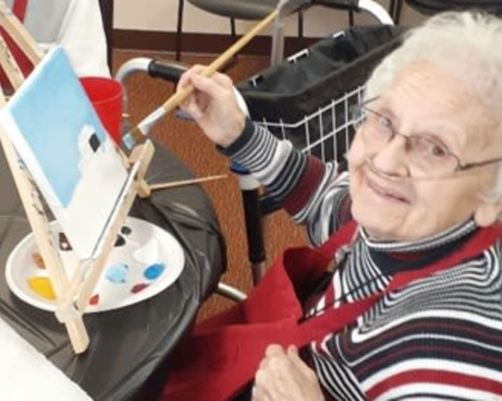 Resident Violet painting a picture for her dare to dream event from Milestone Senior Living in Woodruff, Wisconsin.