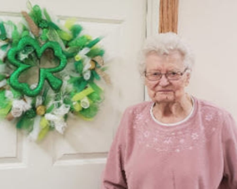 Resident Leona standing next to the wreathe she made for her dare to dream event from SunnyBrook Carroll in Carroll, Iowa.